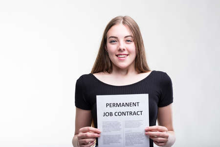 looking towards camera: Smiling successful happy young job applicant holding up a Permanent Job Contract in front of her chest with a beaming smile isolated on white Stock Photo