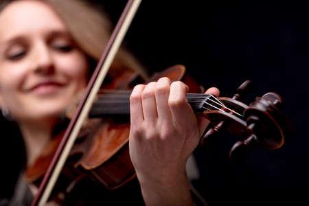 彼女のクラシック音楽の演奏を黒の背景と楽しんで情熱のヴァイオリニスト 写真素材