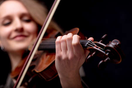passionate violinist playing her classical music instrument on a black background and enjoying Standard-Bild
