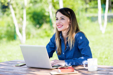 A beautiful, happy, smiling young woman student using a laptop on a park bench while studying in a vibrant outdoor setting.