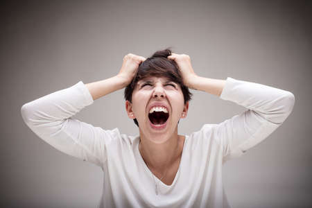 enraged: very enraged woman screaming out while pulls out her hair - angry woman concept