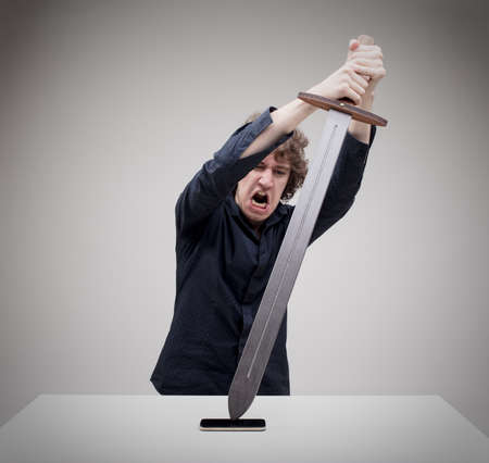 angry man hitting his phone with a sword - concept of technology problems