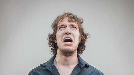 man shouting or cursing with a very angry expression of rage and hate