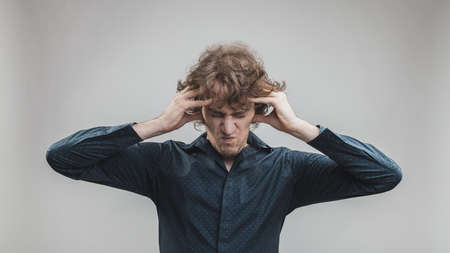man holding his head with his hands because he thinks too much or hes having a headache