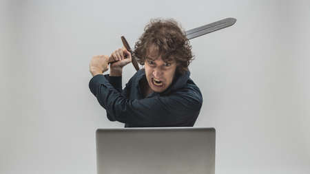angry man about to destroy his laptop computer by hitting it with a medieval sword with an intense expression of rage - concept of computer hassles and worries