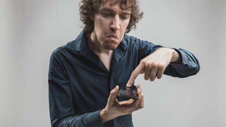 심각한 사람과 어쩌면 걱정하거나 실망 abou 그의 스마트 폰이 예상대로 작동하지 않습니다.