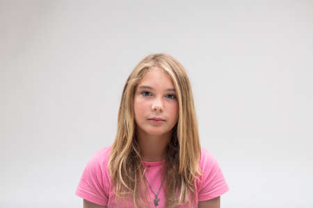 portrait of a very stern and serious little lovely girl on a pink t-shirt on a white background