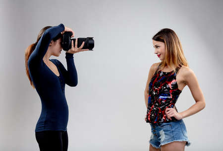 young woman pretending to be a very enthusiastic fashion model photograped by a young woman with her DSLR in a studio environment (gray or white background)