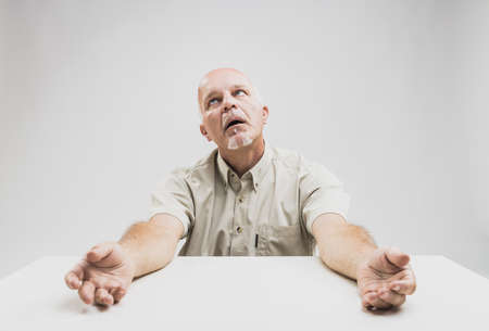 Stressed senior man unable to cope seated at a table with lethargic outstretched arms looking up imploringly with a look of hopelessness