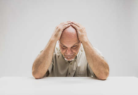 Upset thoughtful balding man sitting at table against plain background