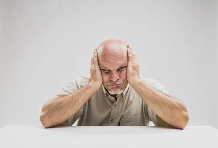 Verbaasde senior man met een glanzende wanhopige uitdrukking aan een tafel staren rechtdoor met zijn hoofd in zijn handen