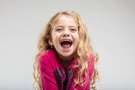Portrait of laughing preteen girl with curly hair against plain background Banco de Imagens