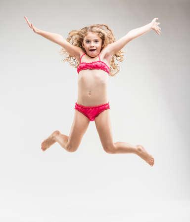 Agile uitbundig klein meisje met lang krullend blond haar in een roze bikini die in de lucht springt met uitgestrekte armen als ze gelukkig glimlacht bij de camera op wit wordt geïsoleerd Stockfoto
