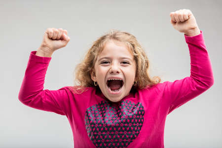 Overjoyed preteen girl raising hands with clenched fists Reklamní fotografie