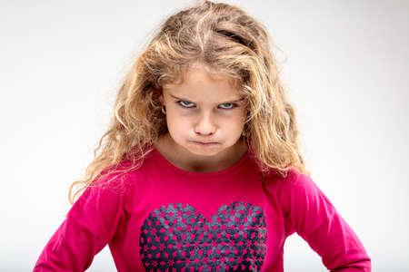 Portret van preteen sulky meisje maken boos gezicht tegen een effen achtergrond