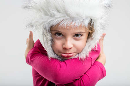 Portrait of preteen girl wearing fluffy winter cap sulking face expression