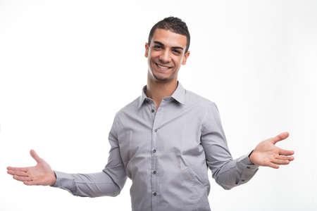 Portrait of young smiling man showing open arms welcoming gesture against white background