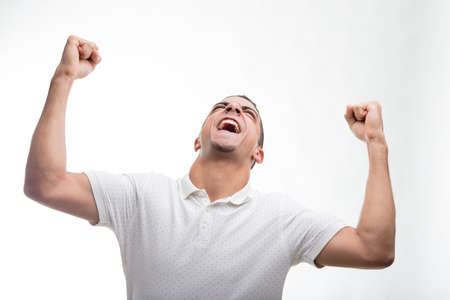 Young man clenching fists with head up in triumphal gesture against white background