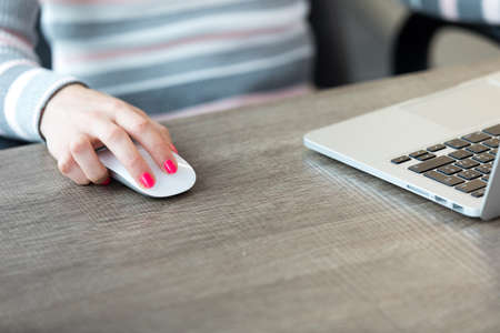 Close up view of woman sitting in front of laptop at desk in office