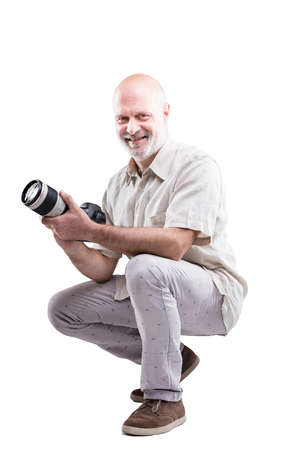 agachado: smiling crouched down professional expert photographer holding his camera in his hands - isolated on white Foto de archivo