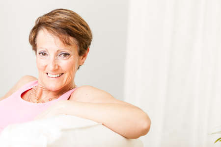 Attractive woman with a lovely friendly smile leaning back on a comfortable sofa looking at the camera
