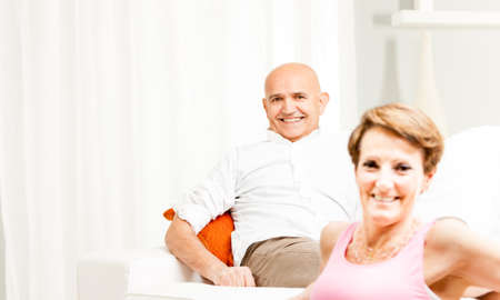 Attractive friendly middle-aged couple relaxing together at home in their living room smiling happily at the camera in a high key image with copy space Stock Photo