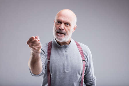 angry old man menacing you with violence and a serious punch Stock Photo