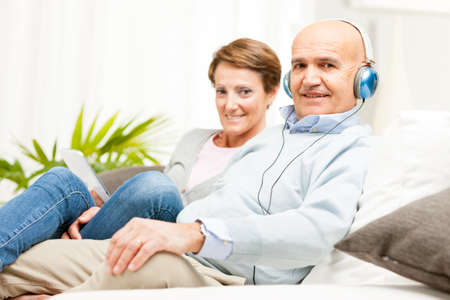Mature affectionate couple relaxing together on a sofa at home listening to music on headphones Stock Photo