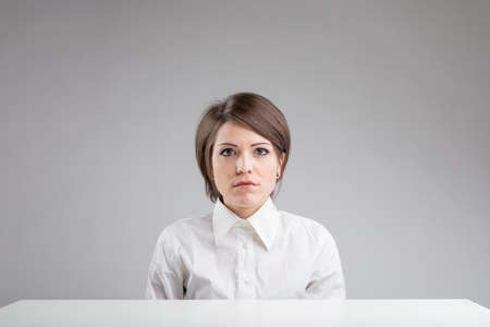 serious inexpressive woman portrait in front of an work table on a gray background with lots of copyspace