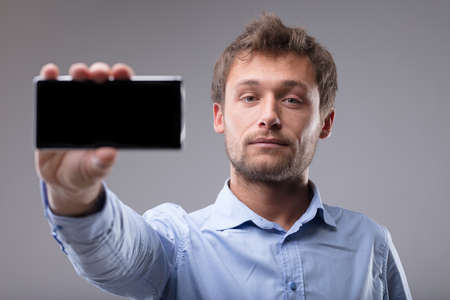 Young bearded man holding out a mobile phone with the screen to the viewer and focus to his face over a grey background