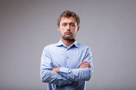 Unemotional man with a deadpan expression standing with folded arms staring at the camera over grey