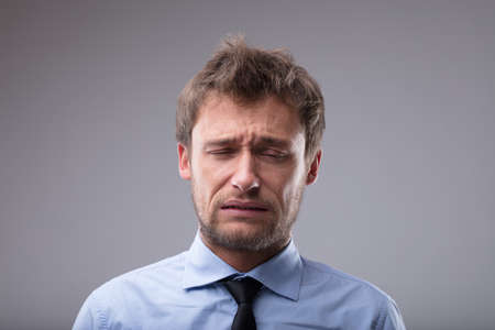 Upset man about to burst into tears grimacing and screwing up his face in a close up head and shoulders portrait over grey Imagens