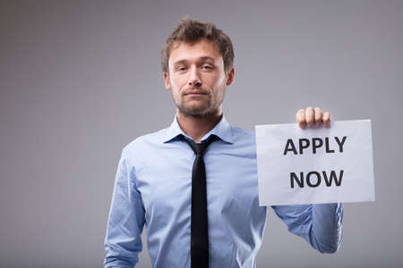 Young businessman holding up an Apply Now sign looking at the camera with a serious expression over grey Imagens