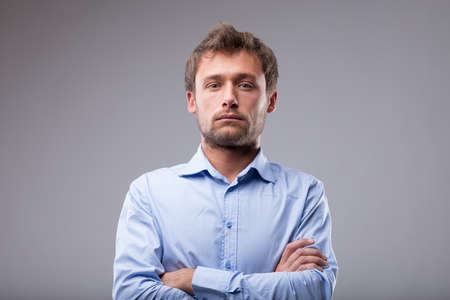 Attractive man with a deadpan expression showing no emotions staring blankly at the camera with folded arms over grey