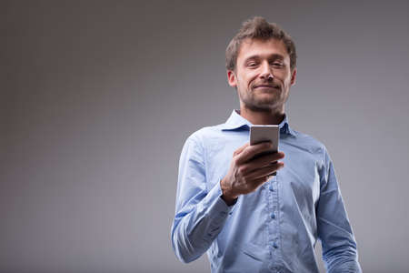 Young man reading a text message on his cellphone or mobile in a low angle upper body view over grey with copy space Imagens