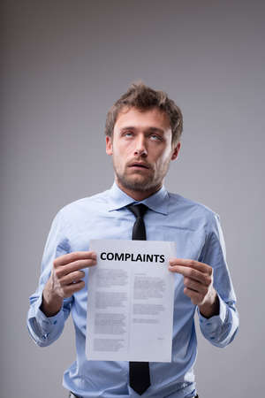 Businessman rolling his eyes over a Complaints notice that he is holding in front of his chest in a conceptual image over grey