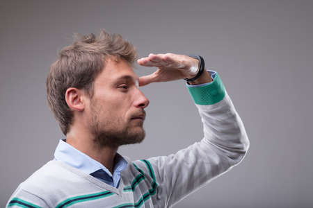 Blond man peering into the distance with his hand raised to his forehead in a closeup profile view over grey