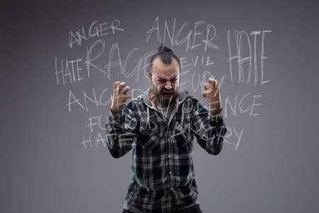 Angry revengeful man in a fit of rage screaming and clawing the air with his fists with a word tag cloud on a chalkboard behind him revolving around anger, hate and rage Stock Photo