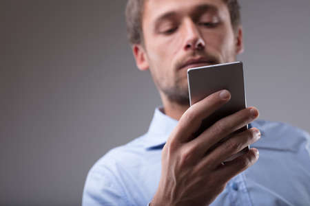 Man reading a message on his mobile phone in a low angle view with close up focus to his hand over a grey background