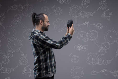 Bearded man with a pony tail taking a selfie holding up a digital camera in front of his face in profile view against a chalkboard with hand drawn cogs for industry and technology