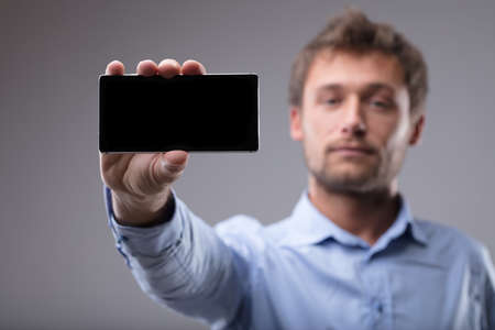 Man holding up a blank mobile phone with the screen to the viewer and focus to the cellphone over grey