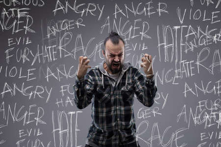 Angry screaming man full of rage and hate clawing the air with his clenched hands with a had written word cloud tag covering his emotions on a chalkboard behind him