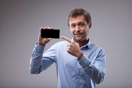 Smiling friendly man pointing to his blank mobile phone which he is holding up in his other hand over a grey background