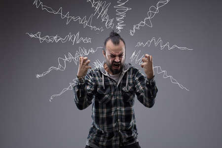 Man in a rage throwing a temper tantrum screaming and clenching his fists with hand drawn squiggles of emotion or sound emanating from his head on a chalkboard behind him Stock Photo