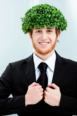 Concept of green business and an eco-friendly businessman wearing a suit with his head covered in fresh green leaves standing grinning at the camera Stock Photo