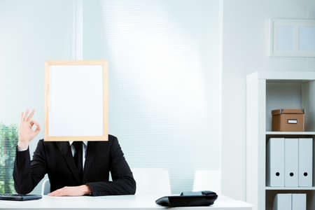 Businessman with a blank picture frame for a face dressed in a smart suit seated at a desk in the office in a conceptual image