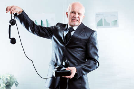 Upset businessman holding a telephone at arms length dangling the receiver from his fingertips with a grimace