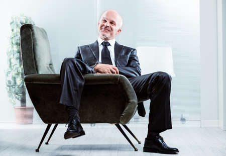 Relaxed successful businessman with a satisfied smile sitting in an armchair with one leg dangling over the side grinning at the camera Stock Photo