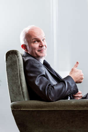 Satisfied happy businessman giving a thumbs up sign with a beaming smile as he sits in a comfortable armchair in a close up cropped view Stock Photo