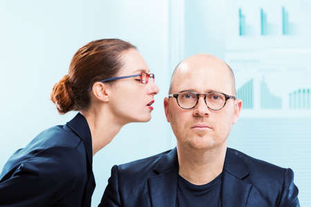 Mobbing concept of businesswoman whispering into man ear at workplace